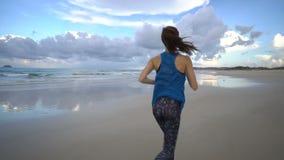 Comienzo atractivo activo sano de la mujer que activa en la playa cerca del mar en puesta del sol metrajes