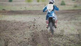 Comienzo del corredor del motocrós que monta su bici del MX de la cruz de la suciedad que golpea para arriba la vista posterior d almacen de metraje de vídeo