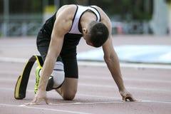 Comienzo explosivo del atleta con desventaja Imagen de archivo libre de regalías