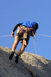 Coming Down. Man abseiling down a rock face royalty free stock photo