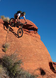 Coming Down. A biker drops down a steep sandstone face Stock Photos