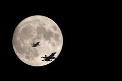 Coming Home. Two F/16 fighter jets silhouetted against a full moon Stock Photo