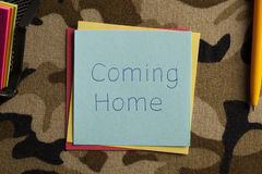 Coming Home written on a note. Top view of Coming Home written note on a camouflage fabric texture stock photo