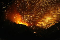 Coming for me. Sparks flying when starting to lance the tap-hole of a submerged arc furnace, with heaps of casting sand to the front, at a South African producer Royalty Free Stock Image