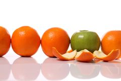 Coming out. Row of oranges and an apple showing its true nature Royalty Free Stock Photo