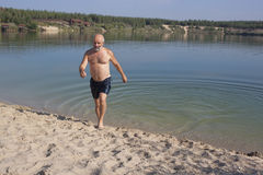 Coming out of the lake on a sandy beach. Mature man with beard in bathing shorts coming out of the lake on a sandy beach royalty free stock images