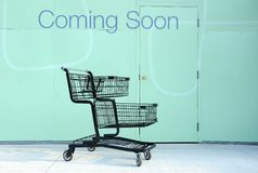 Coming soon. Sign Coming soon written on construction wall and empty cart royalty free stock photography