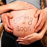 Coming soon. Male and female hands are embracing stomach of a pregnant women on gray background with caption on stomach stock images
