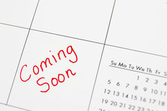 Coming soon. Closeup of a calendar with Coming Soon text in red stock photo