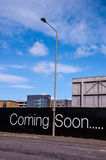 Coming soon billboard on a city road. Coming soon billboard on a road with street lamp and blue sky Royalty Free Stock Image