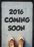 2016 coming soon. Brand new red shoes from above standing on 2016 coming soon sign Stock Photos