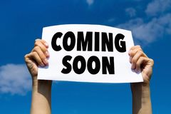 Coming soon. Message note, hands holding paper sign with announcement Royalty Free Stock Photos