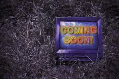 Coming soon concept written on an screen of an old CRT Cathode. Ray tube television - toned image royalty free stock images