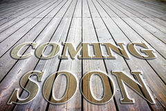 Coming soon concept written on a wooden floor Royalty Free Stock Photography