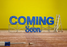 Coming Soon. 3D light blue Coming Soon text with construction tools on yellow background Stock Images