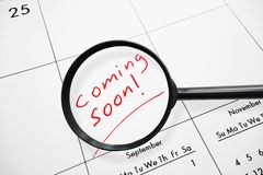 Coming soon enlarged. Magnifying glass looking at Coming Soon text on a calendar Royalty Free Stock Photos