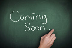 Coming Soon. Hand writing Coming Soon on chalkboard Stock Image