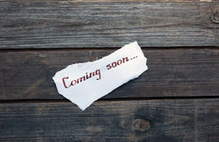 Coming soon hand written on paper piece Stock Photography