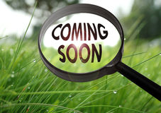 Coming soon. Magnifying glass with the word coming soon on grass background. Selective focus Stock Images