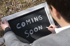 Coming Soon. A man writing a message Coming Soon on a chalkboard with a piece of chalk stock images