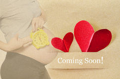 Coming soon. Pregnant woman. With red heart on brown paper tag Royalty Free Stock Photos
