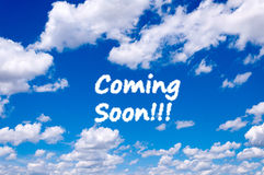Coming soon. Sign clouds on the clear blue sky Stock Photo