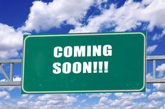 Coming soon. Sign on the green board with clouds in background Royalty Free Stock Photography