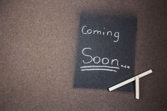 Coming soon sign made chalk on a blackboard. A coming soon sign made chalk on a blackboard Stock Photos