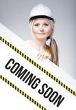 Coming soon sign placed on information board, worker woman Royalty Free Stock Photos