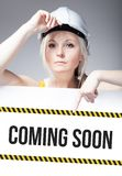 Coming soon sign on template board, worker woman. Coming soon sign on template board with worker woman Royalty Free Stock Photo