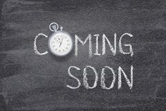 Coming soon watch. Coming soon phrase written on chalkboard with vintage stopwatch used instead of O royalty free stock photo