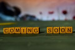 Coming soon on wooden blocks. Cross processed image with bokeh background royalty free stock photos