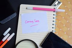 Coming Soon word written on paper. Coming Soon text on workbook, technology business concept stock photo