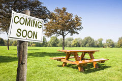 Coming soon written on a signboard near a picnic table. On a green meadow - concept image Royalty Free Stock Photography