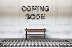 Coming soon written on a wall above a wooden bench - concept ima. Ge royalty free stock image