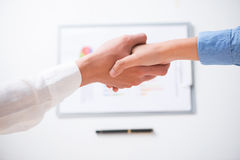 Coming to an agreement. Human handshaking after signing a contract viewed below Royalty Free Stock Photography