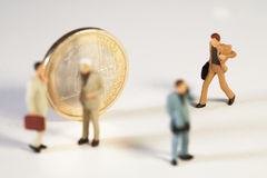 Coming To The Aid Of The Euro. A miniature toy businessman with his briefcase rushes to join his colleagues standing in front of a Euro coin, macro concept Royalty Free Stock Image