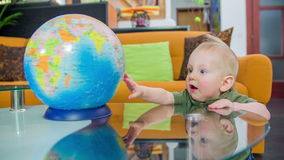 Coming to look at the globe. Young cut boy stands up at the glass table in the living room and looks at the globe on the table, footage in slow motion stock video footage