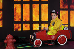 Coming to the Rescue!. A preschool fireman looking at the viewer as he pulls up in a old-time firetruck to a nighttime house fire Royalty Free Stock Images