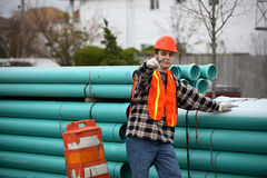 Coming to you. Smiling construction worker standing next to big pile of pipes, pointing at the viewer Royalty Free Stock Photo