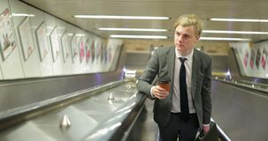 Coming Up the Escalator. Front view, looking down as a young adult businessman comes up the escalator stock video footage