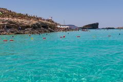 Comino blue lagoon. Tourists enjoying beautiful crystal clear azure turquoise blue waters of the Blue Lagoon on the small holiday island of Comino, Malta, June Royalty Free Stock Images