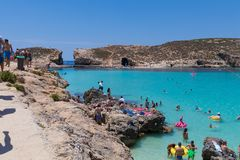 Comino blue lagoon. Tourists enjoying beautiful crystal clear azure turquoise blue waters of the Blue Lagoon on the small holiday island of Comino, Malta, June Royalty Free Stock Photography