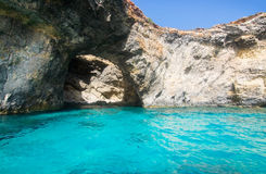 Comino caves. Limestone rock with caves and blue Mediterranean ocean water near Comino island, Malta Stock Photography