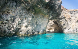 Comino caves. Limestone rock with caves and blue Mediterranean ocean water near Comino island, Malta Stock Photo