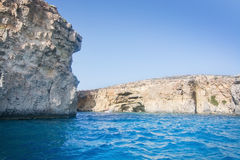 Comino caves. Limestone rock with caves and blue Mediterranean ocean water near Comino island, Malta Stock Images