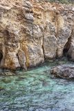 Comino coastline limestone cliffs and the clear Blue Lagoon water, Comino Island, Malta. Comino Island coastline sheer limestone cliffs and the Blue Lagoon Bay Stock Photography