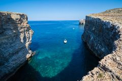 Comino eastern cliffs. Exploring the dramatic huge cliffs and sea caves of east coast of Comino, over looking the deep azure crystal clear waters of the Royalty Free Stock Photos