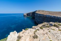 Comino eastern cliffs. Exploring the dramatic huge cliffs and sea caves of east coast of Comino, over looking the deep azure crystal clear waters of the Royalty Free Stock Image
