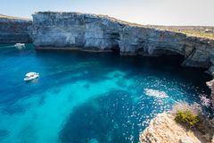 Comino eastern cliffs. Exploring the dramatic huge cliffs and sea caves of east coast of Comino, over looking the deep azure crystal clear waters of the Stock Images